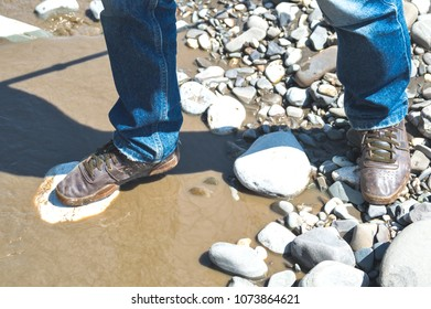 Crossing in shoes the river with dirty water