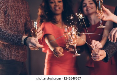 Crossing sticks. Multiracial friends celebrate new year and holding bengal lights and glasses with drink.