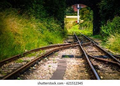 Crossing train tracks. Two metal Railroad tracks crossing with bridge on background. UK transportation system Travel concept. UK travel journey concept. Iron Rail road trails. Two steel train tracks