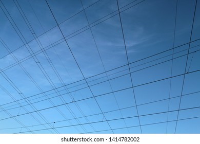 Crossing the wires against the blue sky