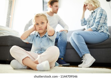 Cross-legged little girl sitting on the floor and covering her ears while parents having quarrel