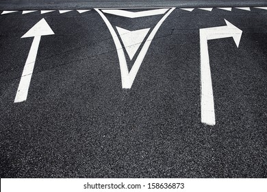 Crossroad choice sign symbols on asphalt.