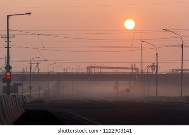 Crossroad, railway overpass and pillars in the fog at morning, Norilsk, August 23, 2018