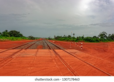 Crossroad of typical bauxite red soils Guinea countryside road and railroad of bauxite mining shuttle trains. Guinea, West Africa.