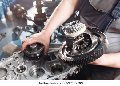 Cross-section of a car gearbox. mechanics work in the garage. hand mechanic in working clothes
