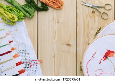 Cross-stitch set : hoop with embroidered flowers pattern, scissors, canvas, colorful threads, color palette and scissors. Wooden background. Hobby, handmade home decor concept. DIY. Copy space