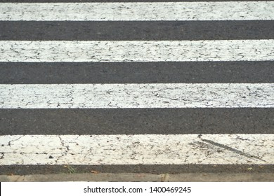 Crosswalk in gray and white in closeup on rough road surface