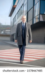 Crosswalk. Mature man in elegant coat looking attentive crossing the street
