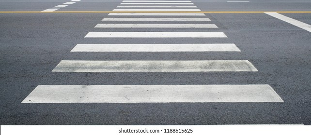 crosswalk on the road for safety when people walking cross the street, Pedestrian crossing on a repaired asphalt road, Crosswalk on the street for safety, logistic import export and transport industry