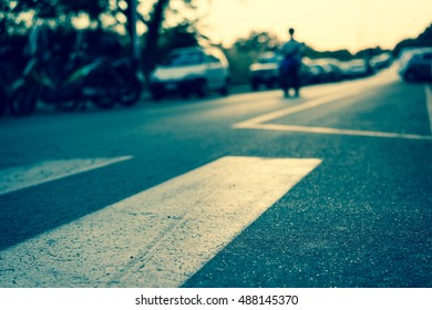 Crosswalk and pedestrian at modern city zebra crossing street with sunset. Blur abstract.Background concept.