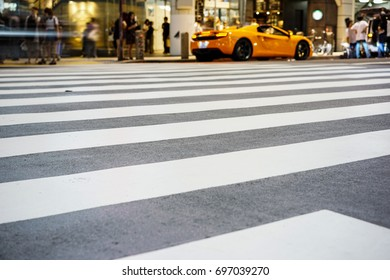 Crosswalk and pedestrian at modern city zebra crossing street with fast moving car lights in the Shibuya Crossing