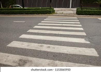 A crosswalk for pedestrians crossing the street. Old crosswalk on the road.