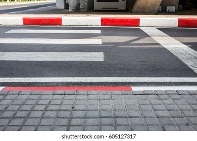 crosswalk with red and white strip at the edge of pavement