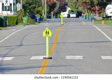 Crosswalk Signs with symbols are posted on an intersection in a residential area near a school.