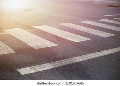 Crosswalk street in urban area with flare of sun light, Zebra crosswalk in town for safety people walking cross the road.