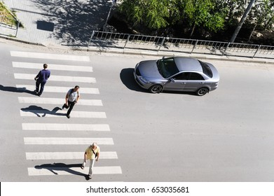 Crosswalk. Top view. Ivano Frankivsk. Ukraine. 23.05.2017. People are crossing a street. A car is waiting for pedestrians.