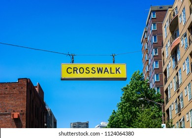 Crosswalk yellow street sign hanging over an avenue in downtown Seattle, USA.