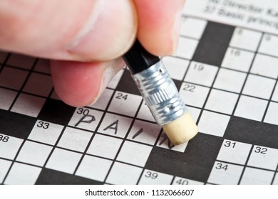 A crossword player erases a word filled in.