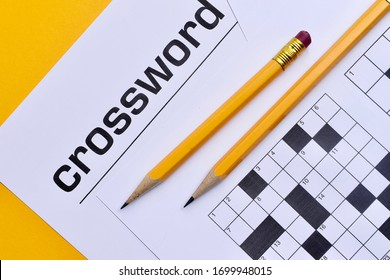 Crossword puzzle and pencils on a yellow background