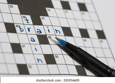 A crossword puzzle saying train and brain. An image of a pencil against an empty crossword puzzle. Crossword puzzles are excellent training for brains.