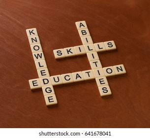 Crossword puzzle with words Skills, abilities, knowledge and education. Learning concept. Ivory tiles with capital letters on mahogany board.