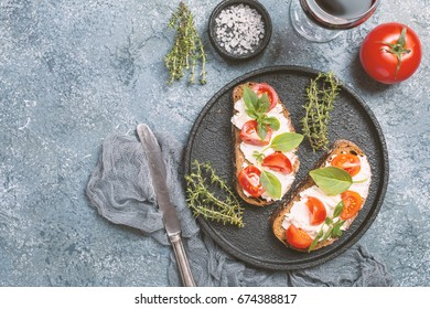 Crostini appetizers with cherry tomatoes, basil, and cheese on gray background, top view on plate