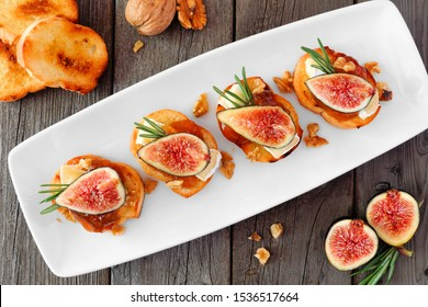 Crostini appetizers with figs, brie cheese and walnuts. Above view on a serving plate over a wood background.