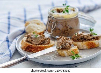 Crostini with beef liver pate, thyme sprigs and a jar of pate on a white stone table, selective focus.
