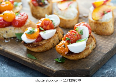 Crostini or bruschetta board with caprese made with roasted tomatoes and fresh herbs