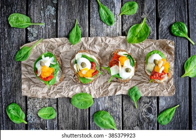 Crostini with mozzarella, sun-dried tomatoes, hummus, fresh spinach, pumpkin, capers and parmesan cheese flakes