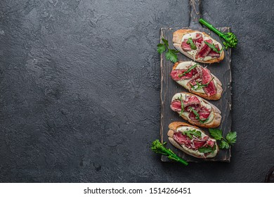 Crostini with roast beef on black board, copy space flat lay