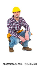 Crouching handyman holding power drill on white background
