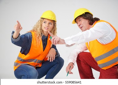 Crouching male and female architects on white background pointing at something