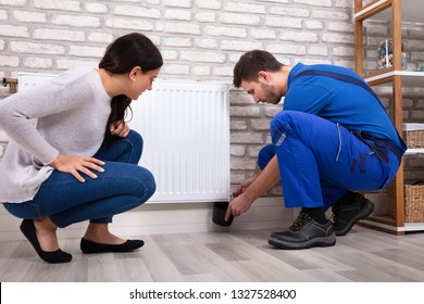 Crouching Woman With Serviceman Turning Radiator Bleed Valve To Release Air With Cup