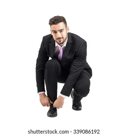 Crouching young businessman tying shoe laces looking at camera. Full body length portrait isolated over white studio background.