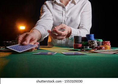 Croupier hands out cards on the background of casino chips