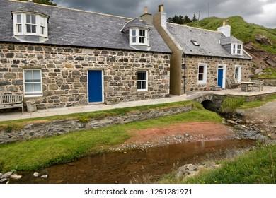 Crovie, Banff, Aberdeenshire, Scotland, UK - June 17, 2018: Stream running under a stone house in coastal fishing village of Crovie Banff Aberdeenshire Scotland UK