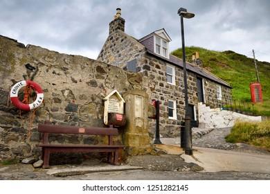Crovie, Banff, Aberdeenshire, Scotland, UK - June 17, 2018: Red Telephone booth and Crovie Pier lifebuoy with stone house in Crovie coastal fishing village Banff Aberdeenshire Scotland UK