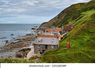 Crovie, Banff, Aberdeenshire, Scotland, UK - June 17, 2018: Single row of houses of Crovie coastal fishing village on Gamrie Bay North Sea Aberdeenshire Scotland UK with red telephone box