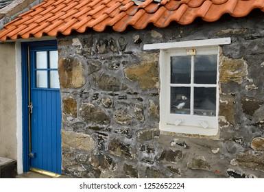 Crovie, Banff, Aberdeenshire, Scotland, UK - June 17, 2018: Stone house with blue door and puffin in window in coastal fishing village of Crovie Banff Aberdeenshire Scotland UK