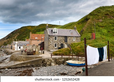 Crovie, Banff, Aberdeenshire, Scotland, UK - June 17, 2018: Single row of houses of Crovie coastal fishing village on Gamrie Bay North Sea Aberdeenshire Scotland UK with red telephone box and washing
