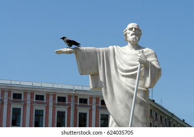 A crow sits on the arm of a marble monument