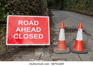 Crowborough, UK - February 24, 2017: A red and white Road Ahead Closed sign with two red and white traffic cones and a country lane in soft focus leading away into the background.