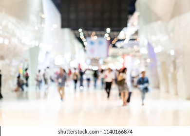 Crowd of anonymous abstract blurred and defocused people at airport, trade fair, convention or trade show exhibition. Bokeh light in event or conference hall background with blurry visitors concept.