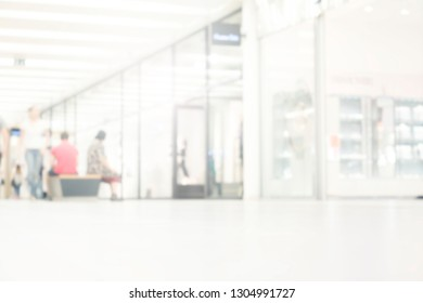 Crowd of anonymous abstract blurred and defocused people at airport, trade fair or trade show exhibition. Bokeh light in event or conference hall background with blurry visitors group concept.