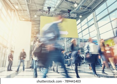 crowd of anonymous blurred people rushing at a trade show