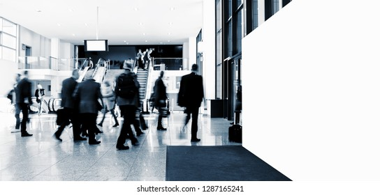 crowd of anonymous blurred people at a trade show, with banner and copy space for individual text