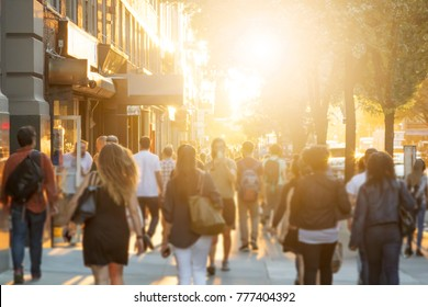 Crowd of anonymous men and women walking down an urban sidewalk with bright glowing sunlight in the background on a busy street in downtown Manhattan, New York City