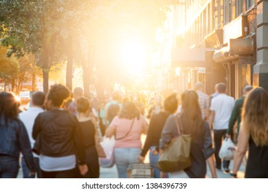 Crowd of anonymous people shopping along a busy sidewalk in New York City with sunlight in the background