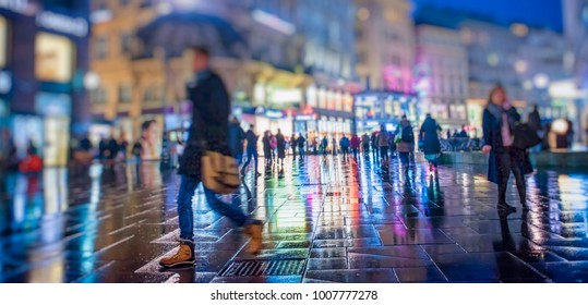 Crowd of anonymous people walking on busy  city night streets